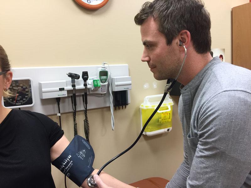 Nurse checking blood pressure of patient